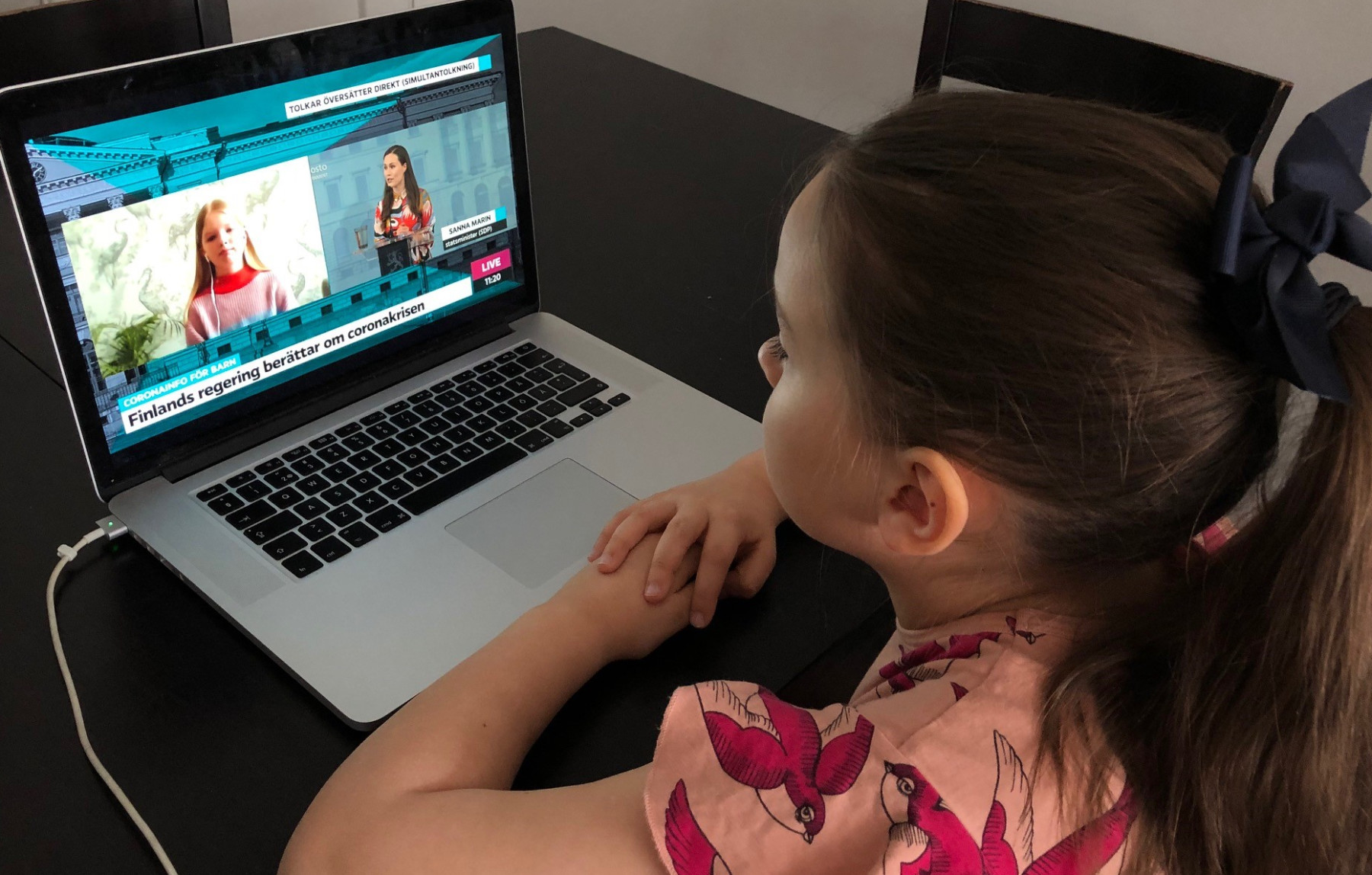 The screen of an open laptop computer shows Finnish Prime Minister Sanna Marin answering the questions of a girl named Iiris, as another schoolchild watches at home.