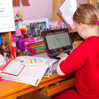A young girl studying on a laptop at her desk, a pile of schoolbooks next to her.