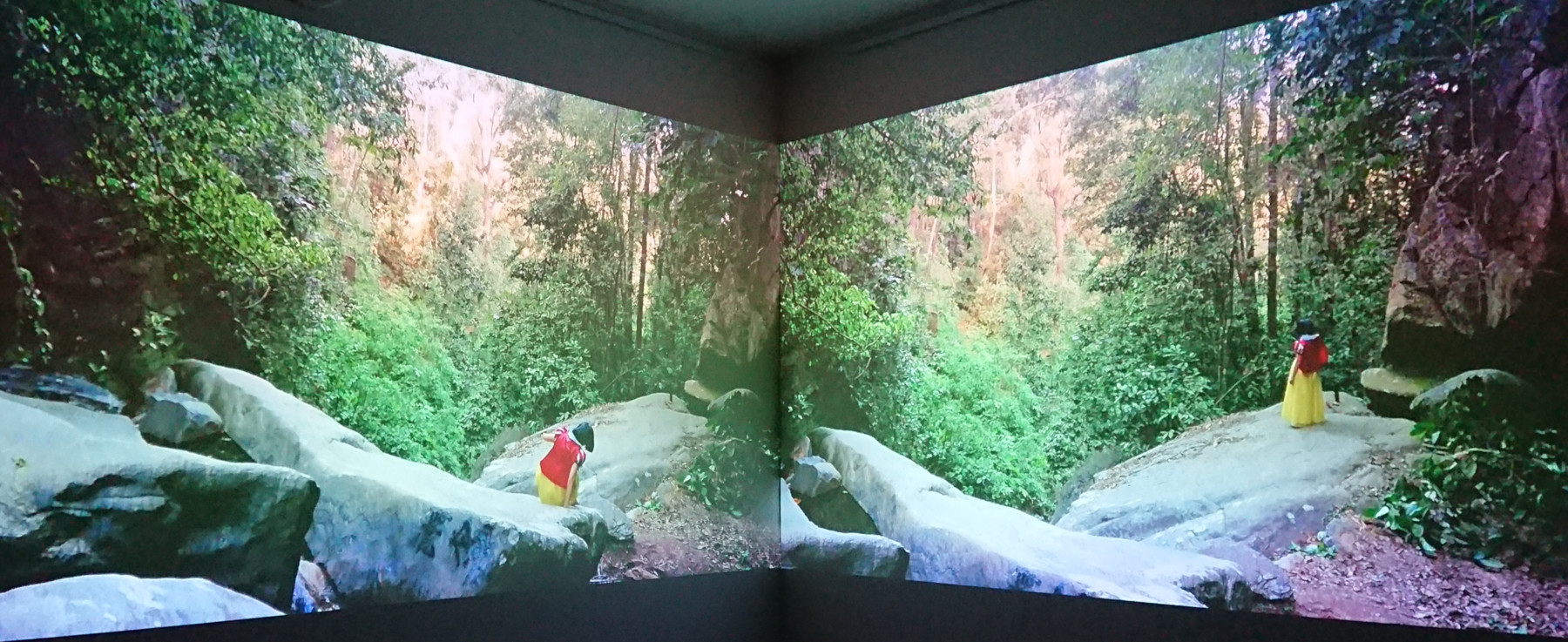 Two screens on a gallery wall showing Ninni Korkalo as Snow White climbing over cliffs in a forest.