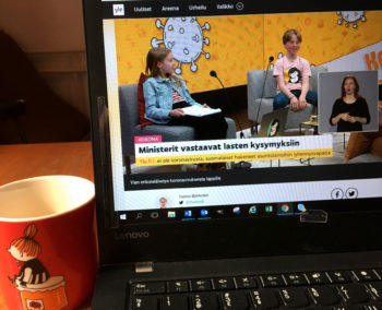 The screen of an open laptop computer shows two children sitting in a TV studio talking into microphones.