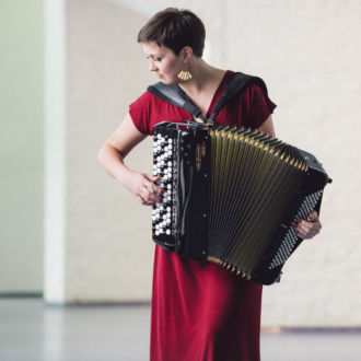 Accordionist Teija Niku plays her accordion in an empty room.