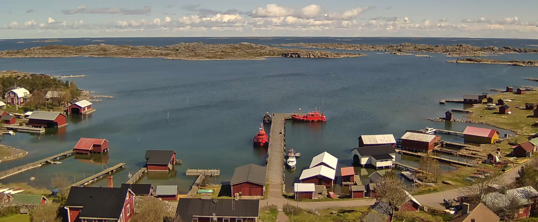 A screenshot of a webcam image showing the ocean harbour of Utö Island with small cabins and boats.