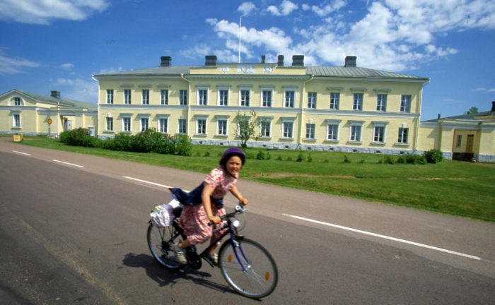 A girl bikes past a long, stately, two-storey building on a summer's day.