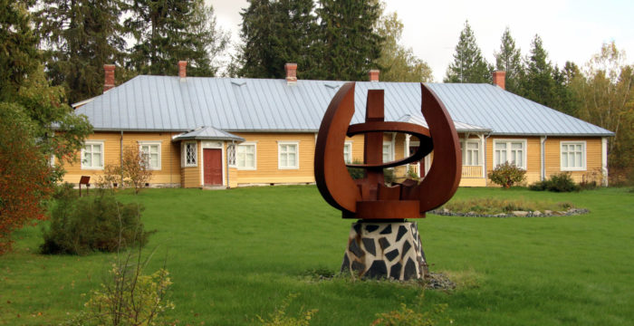 A wooden building stands in a rural setting. An angular metal sculpture stands in front of the building.