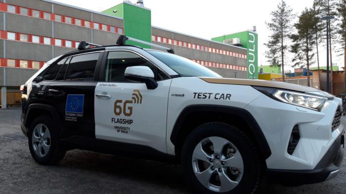 Автомобиль с надписями на боку «6G Flagship» и «Испытательный автомобиль» припаркован у здания Университета Оулу.