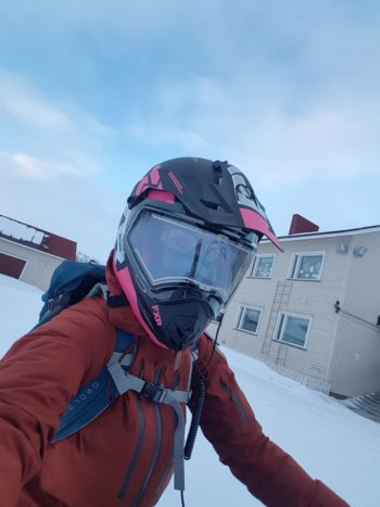 A woman with a helmet, goggles and a backpack takes a self-portrait in front of a school building and a snowy schoolyard.