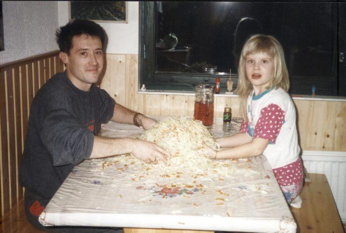 Алина Томников сидит за столом со своим отцом и квасит капусту.