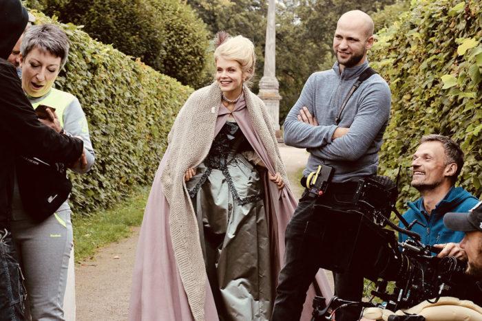 На съёмках сериала «Екатерина. Самозванцы». На фото четыре человека, крайне справа мужчина с камерой, вторая слева актриса Алина Томников в костюме XVIII века.