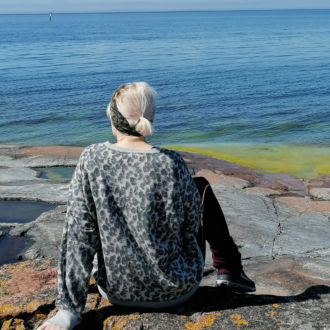 With her back to the camera, a woman sits on a rocky shore looking at a wide expanse of ocean and sky.