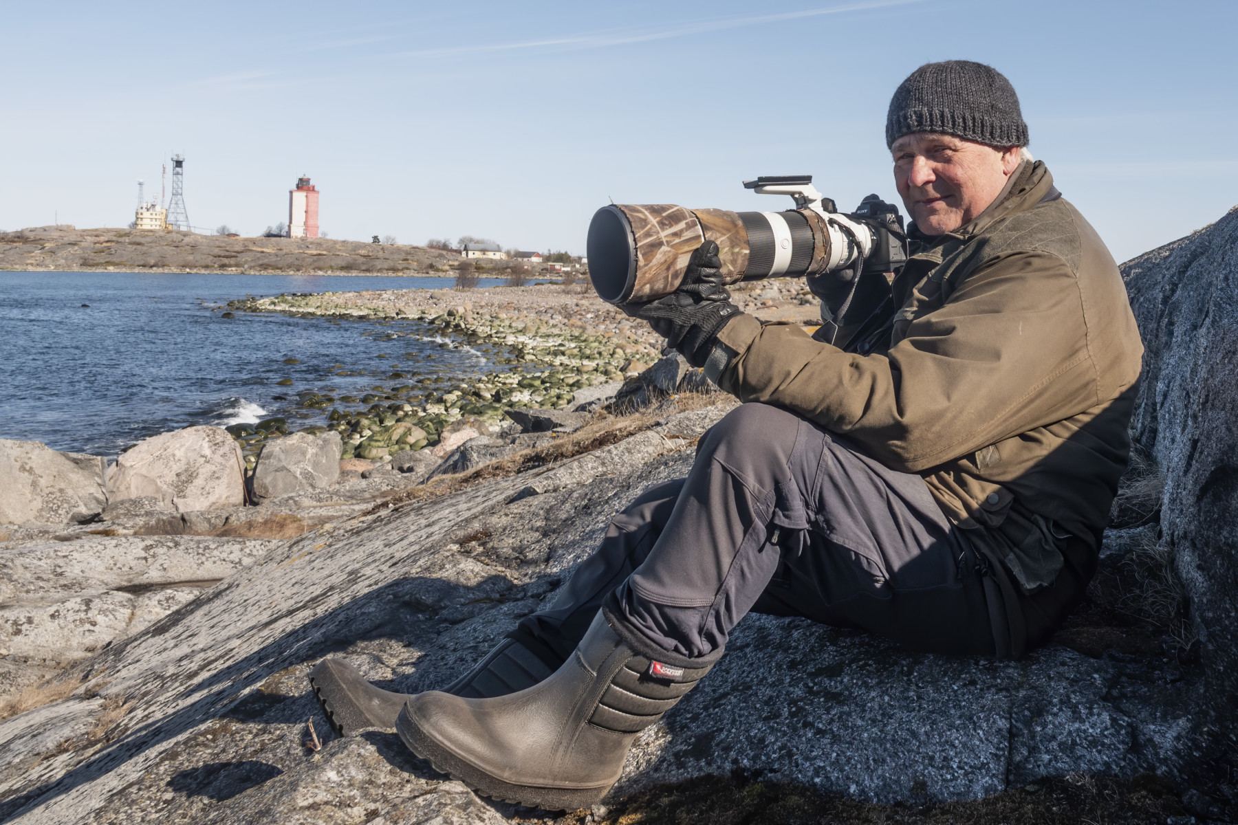 A man sits on a rocky ocean shoreline and adjusts a camera with a long lens.