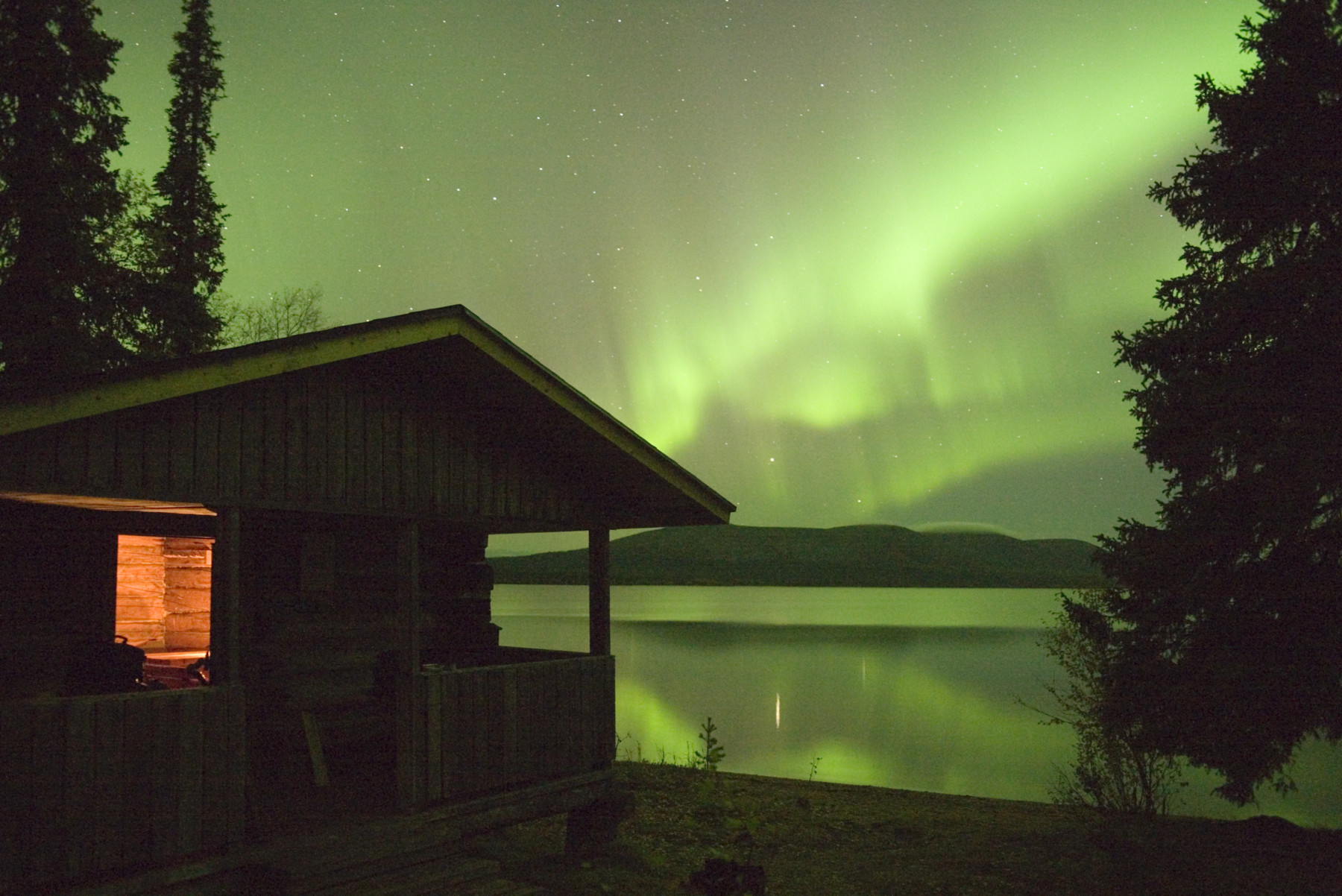 A cabin by a lake at night, with the sky full of wavy green patterns from the Northern Lights.