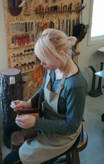 A woman sits on a chair and works on a piece of leather in a workshop with tools hanging on the wall.