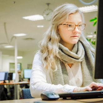 A woman types on a computer keyboard in a library.