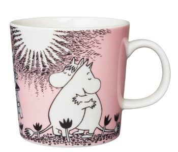 A pink mug that has a picture of two Moomin characters hugging each other while the sun is shining.