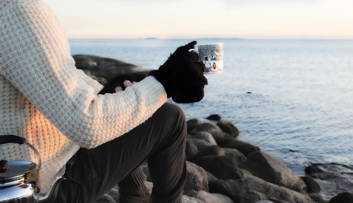 A man wearing a white jumper is sitting on a rock by the sea while holding a Moomin mug in his hand.