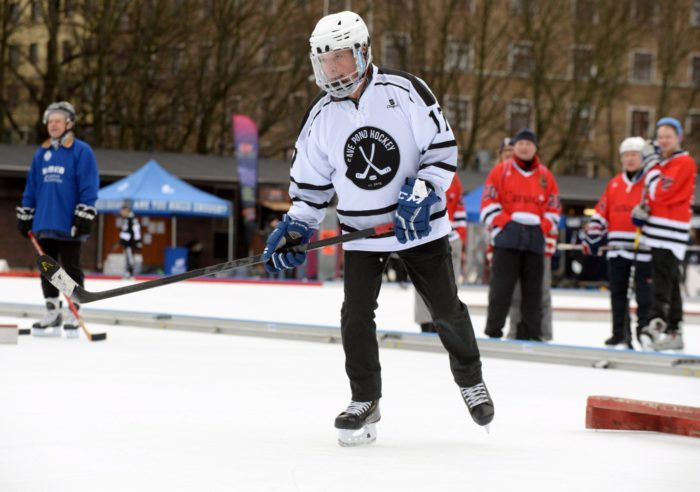 Finnish President Sauli Niinistö, in a helmet and a jersey that says Save Pond Hockey, skates with a hockey stick on an outdoor ice rink while other players are visible in the background.