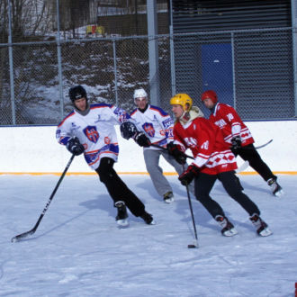 Five ice hockey players skate after the puck on an outdoor ice rink.