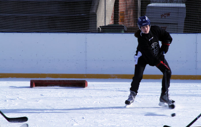 A woman ice hockey player dribbles the puck on an outdoor ice rink while the hockey sticks of several opponents are visible in the corners of the picture.