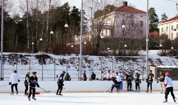 An ice hockey game takes place on an outdoor ice rink in front of a hillside where there are trees and buildings.