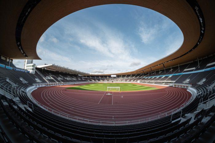 体育场内景,显示出绿茵、观众席上方的顶棚,以及顶棚边缘露出的天空。
