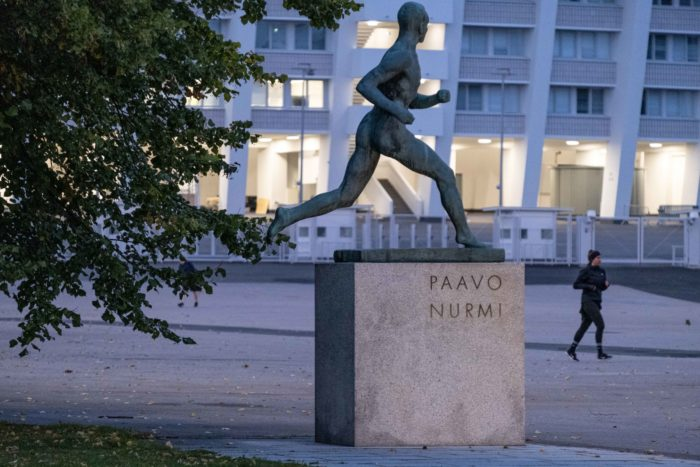 A statue of a running man is on a pedestal in front of a stadium, and a jogger is running past it.