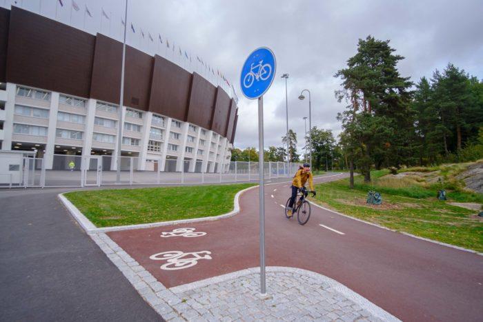 Un ciclista pasa por delante de un estadio, pedaleando por un carril bici de aspecto nuevo y funcional.