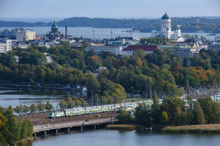 Una vista de Helsinki con la bahía, un tren que pasa, un parque lleno de árboles y cúpulas de iglesias.