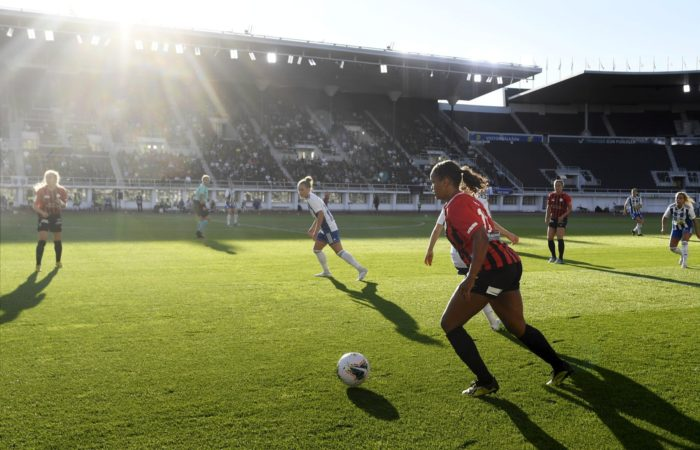 Players run up the field in a women's football match in a stadium.