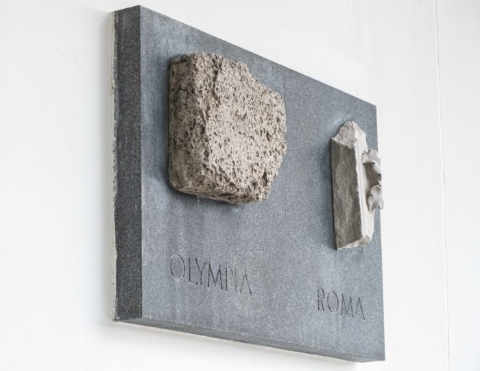 Two chunks of stone are mounted on a plaque on a wall.