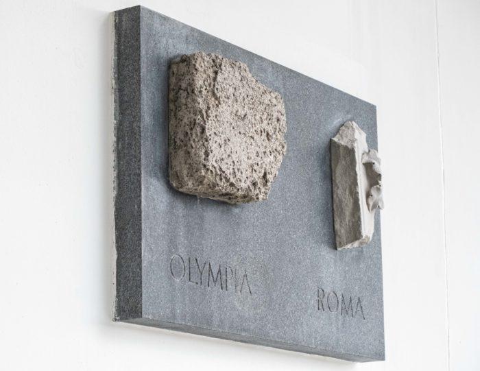 En una pared hay una placa con dos trozos de piedra enmarcados en ella.