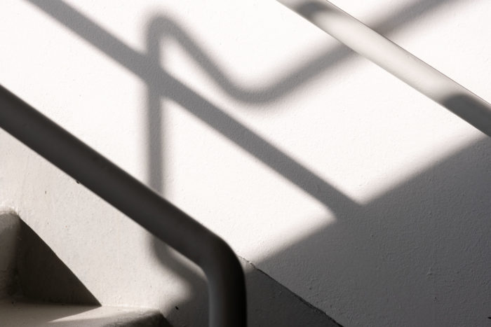 Long thin shadows fall from metal railings across a white space.
