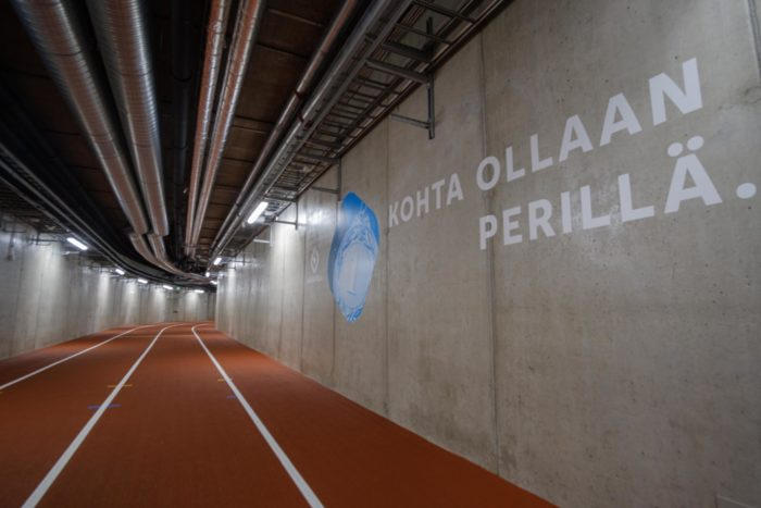 """Beside an indoor stretch of running track, a sign on the wall says, """"Nearly there,"""" in Finnish."""