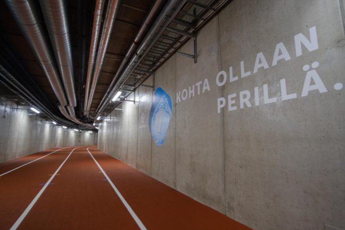 """在一段室内跑道旁边,墙上的芬兰语字幕显示""""快到了""""。"""