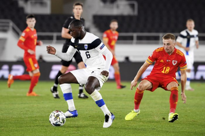 在一场国际男子足球比赛中,一名球员在控球,对方一名球员企图拦截他。