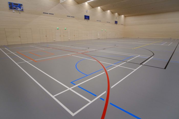 A gymnasium floor shows lines of various colours for various sports.