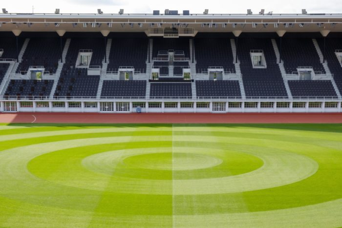 背景中有成排的体育场座椅,前景是足球场的绿茵。