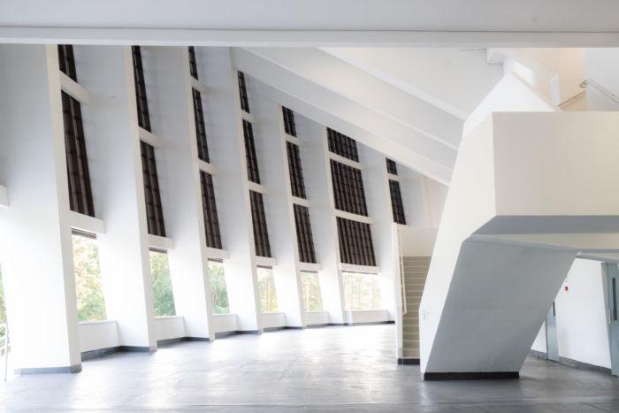 Un gran vestíbulo interior con dos escaleras blancas a uno de sus lados.