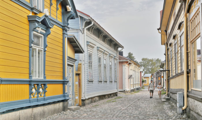 Two people walk down a cobblestone street between old-fashioned wooden houses.
