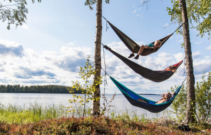 Three people lie in hammocks that are strung one above the other between two trees.