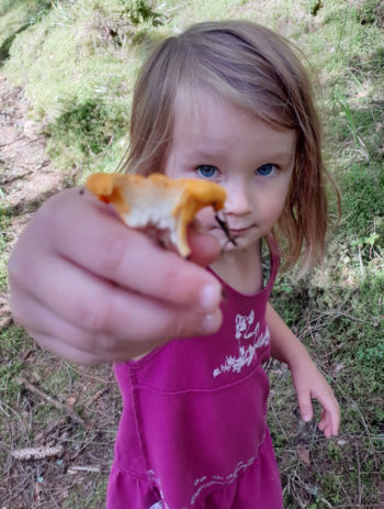 A girl holds up a mushroom she has picked in the forest.