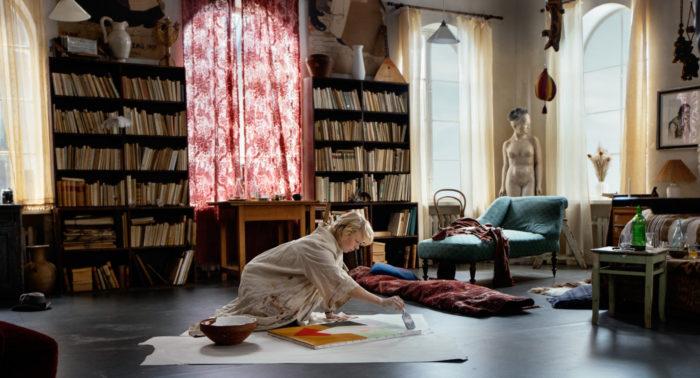 Uma mulher pinta em uma tela no chão de uma grande sala com estantes de livros ao fundo.