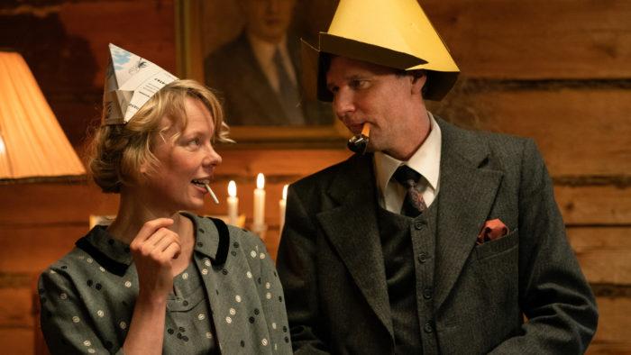 Uma mulher e um homem usando chapéus de festa pontudos se entreolham.