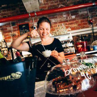 Бариста в кафе наливает молоко в чашку. На переднем плане бутылки и хлебобулочные изделия.