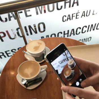 Две чашки кофе с молоком на столе в кафе, человек фотографирует чашки на свой телефон. На заднем плане названия разных видов кофе.