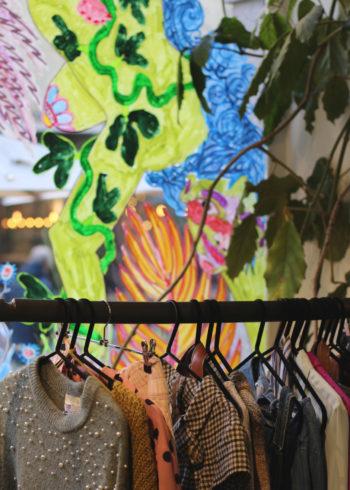 Des vêtements sont accrochés à un portant installé devant une vitrine sur laquelle ont été peints des motifs multicolores.