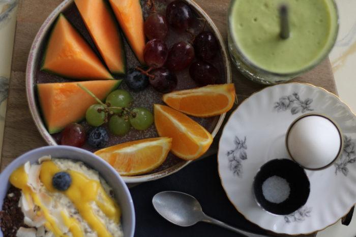 Une photo prise au-dessus d'une table montre deux bols remplis de porridge pour l'un, de quartiers de melon et de raisins pour l'autre, une assiette sur laquelle est posé un œuf à la coque et une coupelle contenant un smoothie de couleur verte.