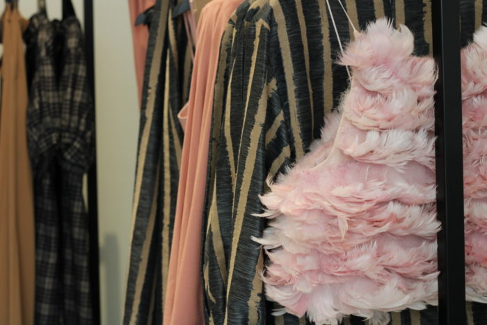 Des vêtements vintage chic pendent sur un portant dans un magasin.