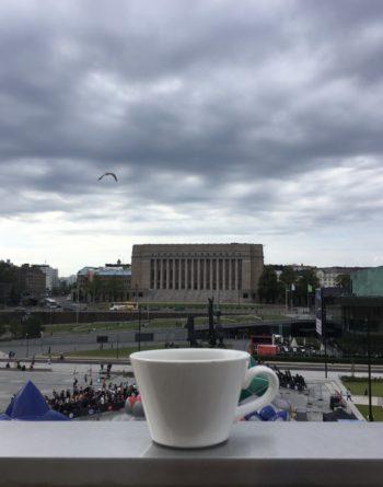 Чашка кофе на фоне здания парламента Финляндии.