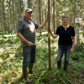 A man and a woman stand in the forest, each with one hand on a tall wooden pole that is stuck in the ground.