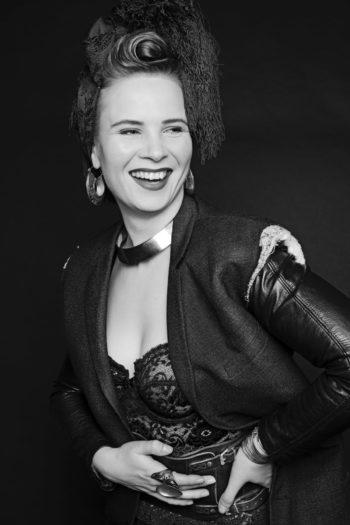 Une jeune femme souriante vêtue d'une veste en cuir et portant des bijoux prend la pose pour le photographe une main posée sur sa hanche, l'autre à hauteur de sa ceinture.